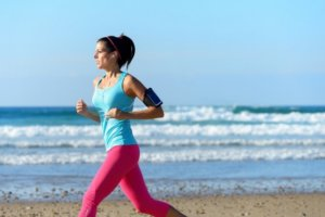イヤホンで音楽を聞きながら走る女性