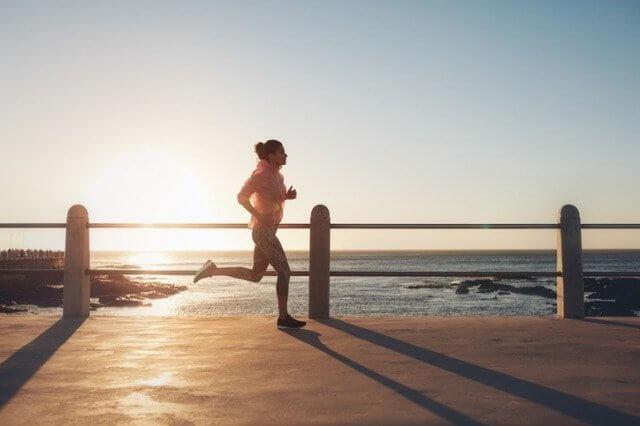 夕日の中走る女性