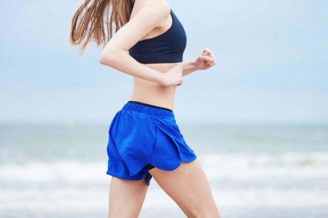 ランニング用スポーツショーツを履いて走る女性