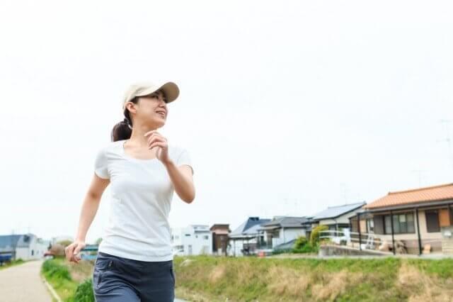 ランニングキャップを被ってジョギングする女性