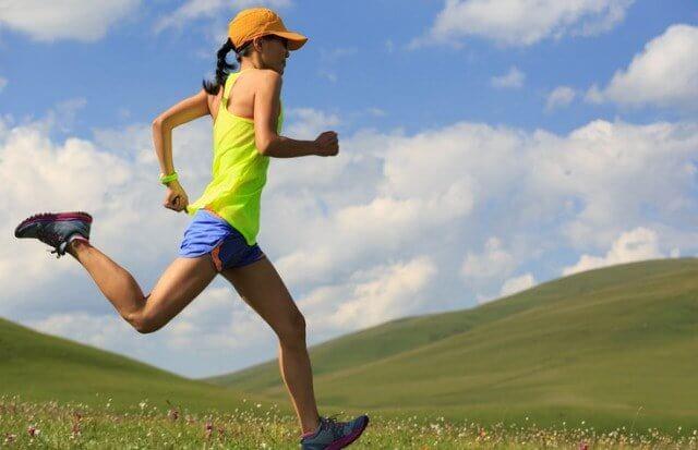 強い日差しの中ランニングキャップを被って走る女性