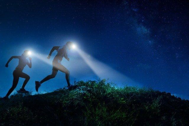 夜間にヘッドライトで足元を照らすランナー