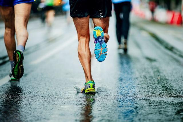 雨の中走る男性ランナー