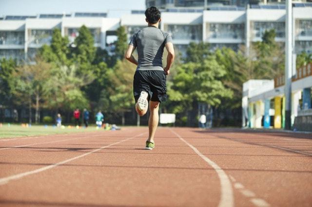 陸上競技場を走る陸上選手