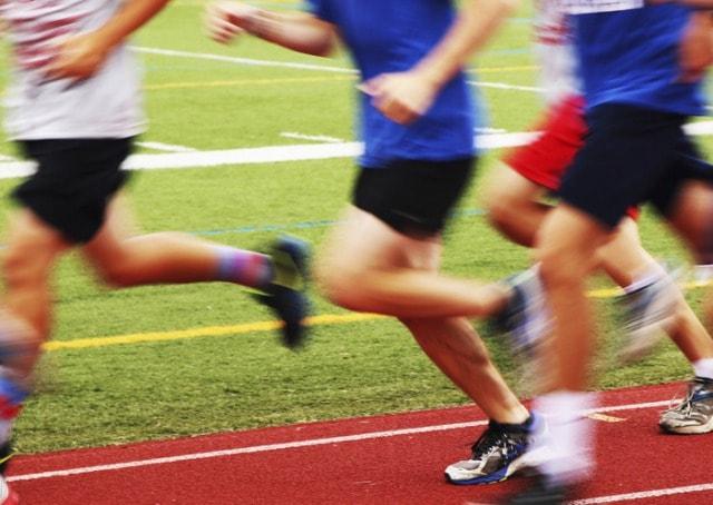 陸上競技場を走る選手達