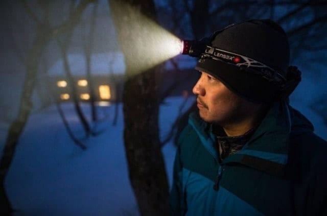 夜のトレイルをヘッドライトで照らす人