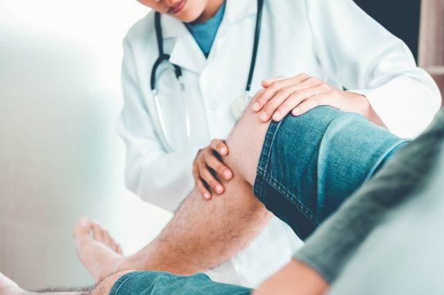 病院で医師に膝を見てもらっている人