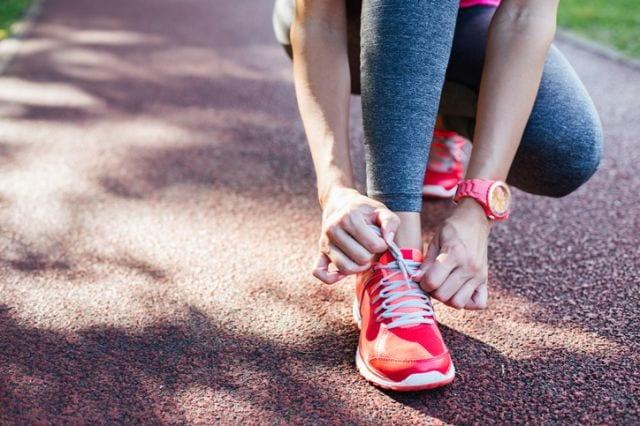 練習へ向けて靴紐を結ぶランナー