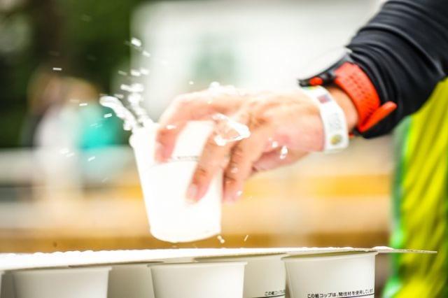 マラソンの給水所でコップを取るランナー