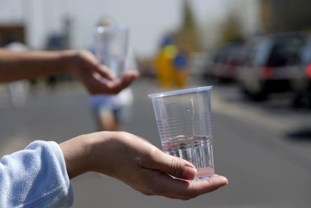 給水用コップを持つ人の手