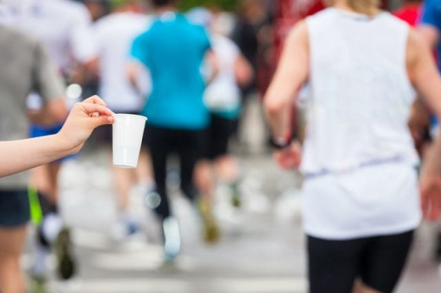 マラソンランナーに水の入ったコップを差し出す人