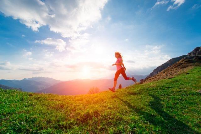 山の開けた道を走る女性