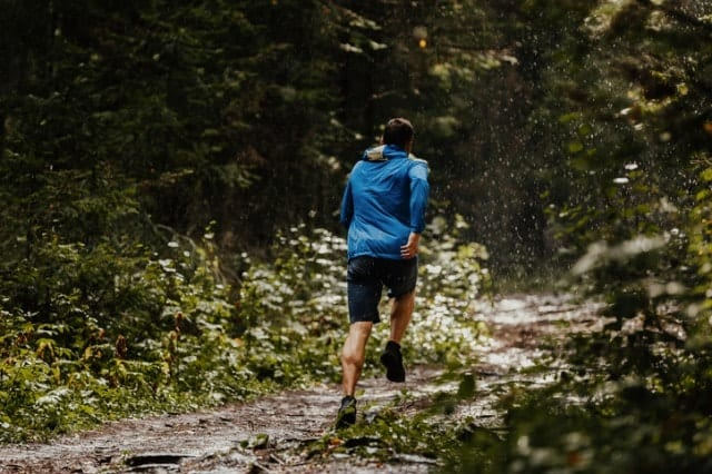 雨の中、レインウェアを着て走る人