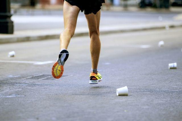 コップをよけながら走るマラソンランナー