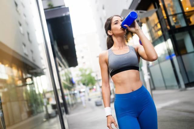 スポーツ中にスポーツドリンクを飲む女性