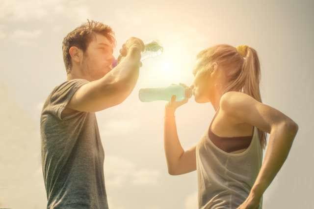 ランニング中に水分補給をする男女