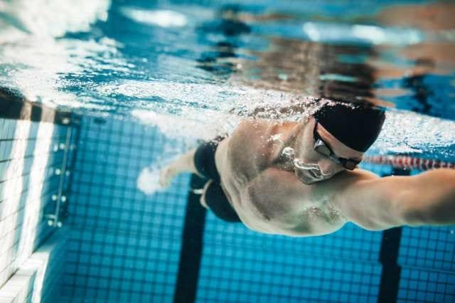 プールで水泳をする男性