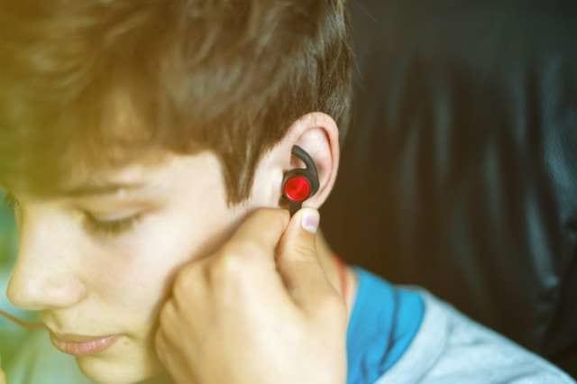 スポーツイヤホンを耳に装着する人