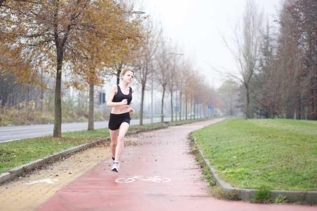 雨の中走り続ける女性
