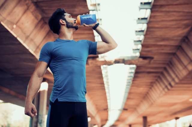 走り終えた後にプロテインを飲む男性