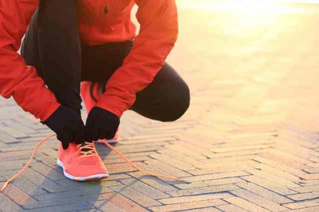 手袋を着用して靴紐を結ぶ人