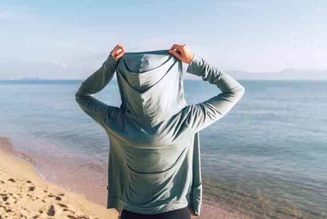 海辺でラッシュガードを着用した人