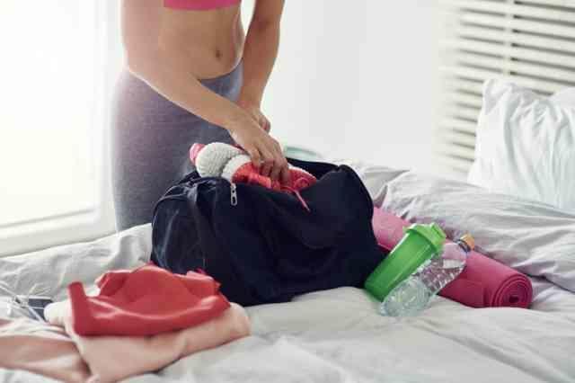 スポーツバッグに荷物を詰める女性