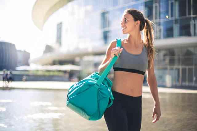 ジムバッグを持つフィットネス姿の女性