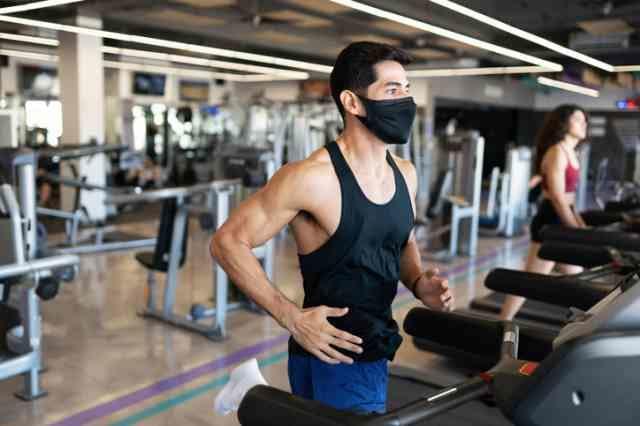 ジムでマスクを着用して走る男性