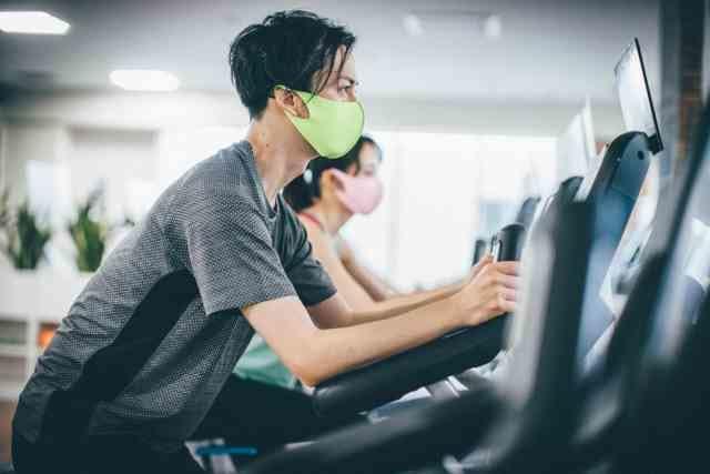 トレーニングとしてエアロバイクを漕ぐ男性