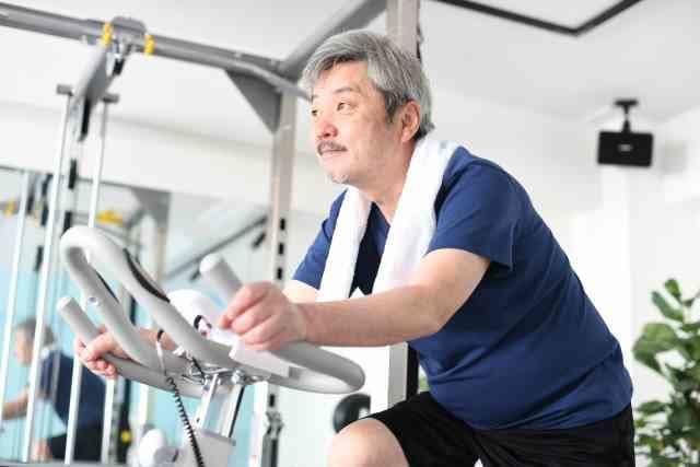 健康のためにエアロバイクを漕ぐ男性