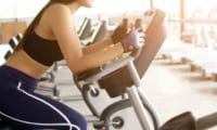 スポーツジムでエアロバイクをする女性