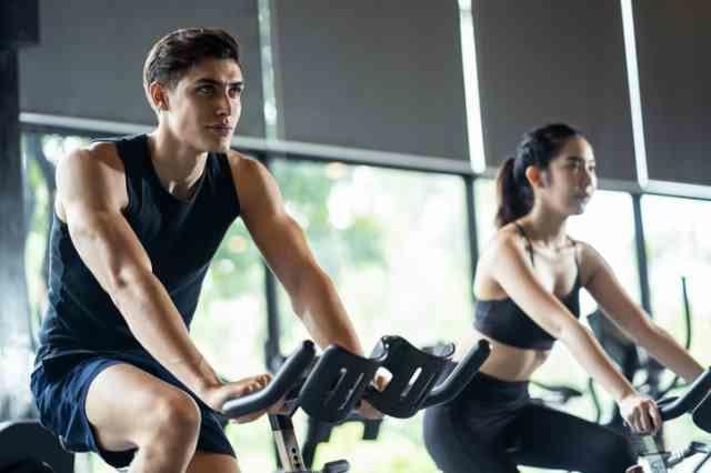 背筋を伸ばした姿勢でエアロバイクを漕ぐ男女