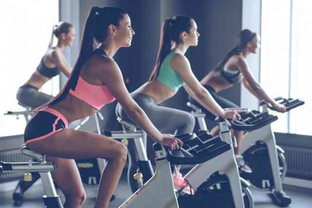 ダイエットのためにエアロバイクを漕ぐ女性たち