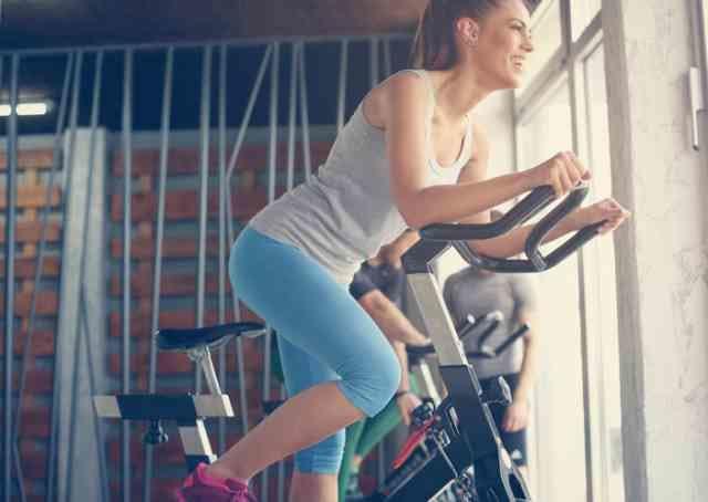 エアロバイクでダイエットに励む女性