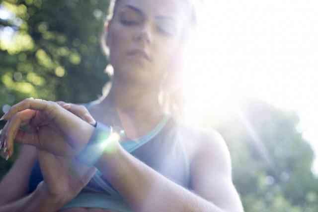 屋外でランニングウォッチの画面を見る女性