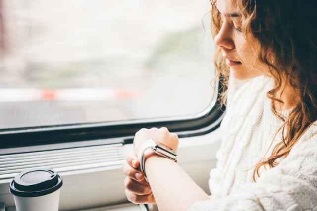 電車に乗りスマートウォッチを見る女性
