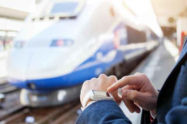 スマートウォッチを操作しながら電車を待つ人