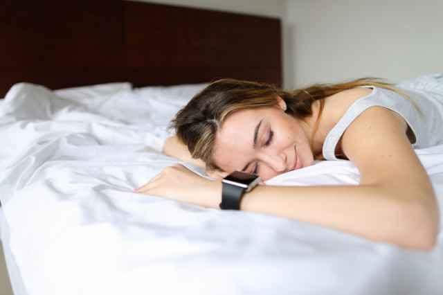 スマートウォッチを装着して寝る女性